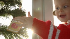 The little girl in the red dress decorating Christmas tree with a gingerbread. Stock Footage