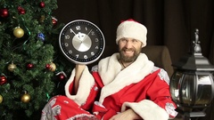 Bad brutal Santa Claus smiling and shows the clock, five minutes to twelve, on Stock Footage