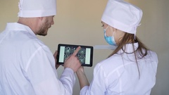 Male and female doctors examine X-rays on the tablet Stock Footage