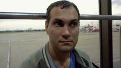 Portrait of tired man waiting for flight at airport. Airplane delay Stock Footage
