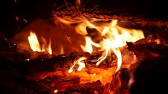 Glowing Fire Licking Wooden Log with Sparks Flying in Slow Motion MOV Stock Footage