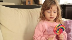 Funny little girl with long, curly hair holding big colorful Lollipop Stock Footage
