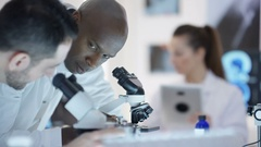 4K Research scientists in the lab, working with microscopes & tablet computer Stock Footage