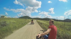 A young man riding a quad bike on a field and shoots on selfie sticks himself Stock Footage