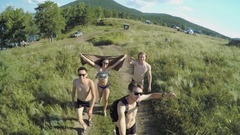 Group of young people in bathing suits walking on the field Stock Footage
