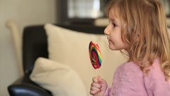 Little girl eating and licking with tongue big multicolor spiral lollipop can Stock Footage