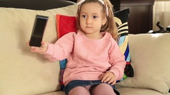 Little girl watching television Stock Footage