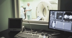 CT MRI scanner room doctor talks patient 4k video. Screen result diagnosis Stock Footage