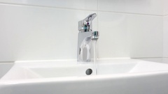 Bathroom sink and faucet with water running. Stock Footage