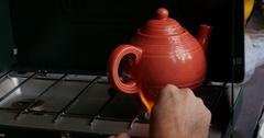 Orange Ceramic Tea Pot on Camp Gas Grill, 4K Stock Footage