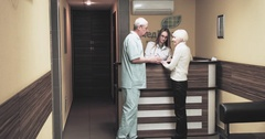 Doctor speaks with female patient at hospital reception 4k video. Elderly woman Arkistovideo