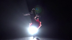 Long-haired girl dancing rumba on a dark background with light illuminator. Slow Stock Footage