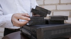 Man's long-selects and loads tape into old VCR. Black vintage video recorder. Stock Footage