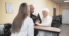 Elderly patients talking nurse receptionist at hospital reception desk 4k video Stock Footage