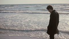 A young man is walking on a beautiful beach with his jeans rolled up and soaking Stock Footage