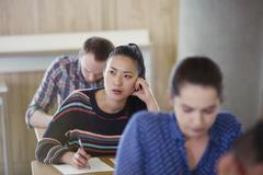 Pensive female college student taking test in classroom Stock Photos