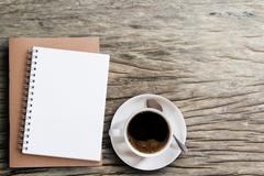 Blank notepad and coffee cup on wooden Stock Photos