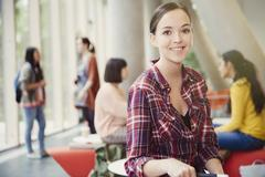 Portrait smiling female college student in commons Stock Photos