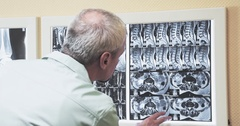 Male doctor reviewing CT MRI images 4k video. Looks on x-ray scan image Stock Footage