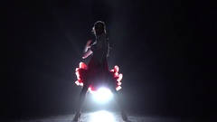 Girl dancing samba on a dark background with light illuminator. Slow motion Stock Footage