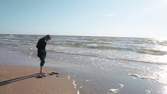 A young man is standing barefoot on a beautiful sandy beach and digging a hole Stock Footage
