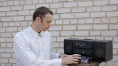 The man inserts the cassette in black cassette player and push Play. Stock Footage