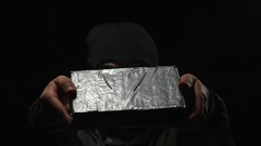 4K Criminal Showing a Cocain Drug Brick - Black Background Stock Footage