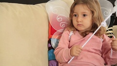 Portrait of a cute little girl with angel wing watching tv Stock Footage