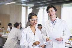 Portrait confident college students in lab coats in science laboratory classroom Stock Photos
