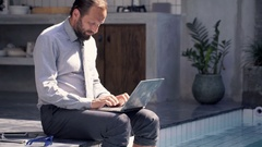 Businessman finishing working on laptop and relaxing by pool in outdoor villa Stock Footage