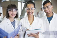 Portrait smiling college students in science lab coats Stock Photos