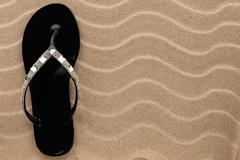 Flip-flop black so strass on sand Stock Photos