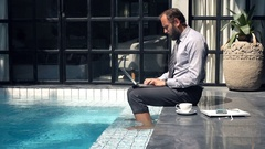 Young businessman working on laptop sitting by pool in outdoor villa Stock Footage