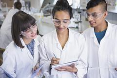College students in lab coats discussing notes in science laboratory classroom Stock Photos