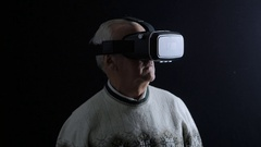 Senior Man wearing virtual reality goggles. Studio shot, dark room Stock Footage