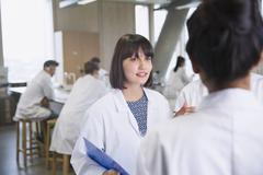 Female college students in lab coats talking in science laboratory classroom Stock Photos