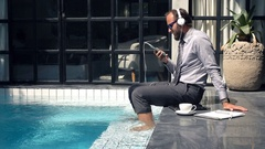 Happy businessman listening to music on cellphone by pool in outdoor villa Stock Footage