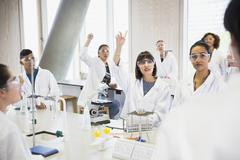 College students raising hands in science laboratory classroom Stock Photos