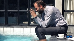 Happy businessman playing game on smartphone by pool in outdoor villa Stock Footage