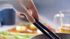 In the kitchen a woman is cooking bratwurst in a frying pan using the tongs Stock Footage