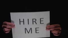 4K HIRE ME Sign Being Hold By Hands - Black Background Stock Footage