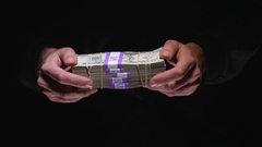 4K Hands Showing Huge Cash Money Stack - Black Background Stock Footage