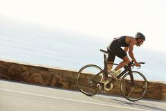 Male triathlete cyclist racing on ocean road Stock Photos