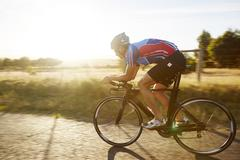 Male cyclist cycling on sunny sunrise rural road Stock Photos