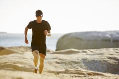 Male triathlete running on sunny rocky trail Stock Photos