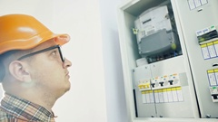 Young adult electrician builder engineer checking equipment in fuse box Stock Footage