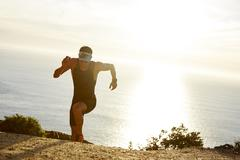 Male triathlete runner running uphill on sunny ocean trail Stock Photos