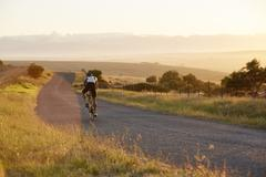 Male triathlete cyclist cycling on sunny rural road at sunrise Stock Photos