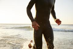 Male triathlete swimmer in wet suit running out of ocean surf Stock Photos