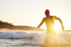 Male triathlete swimmer in wet suit running out of sunny ocean Stock Photos